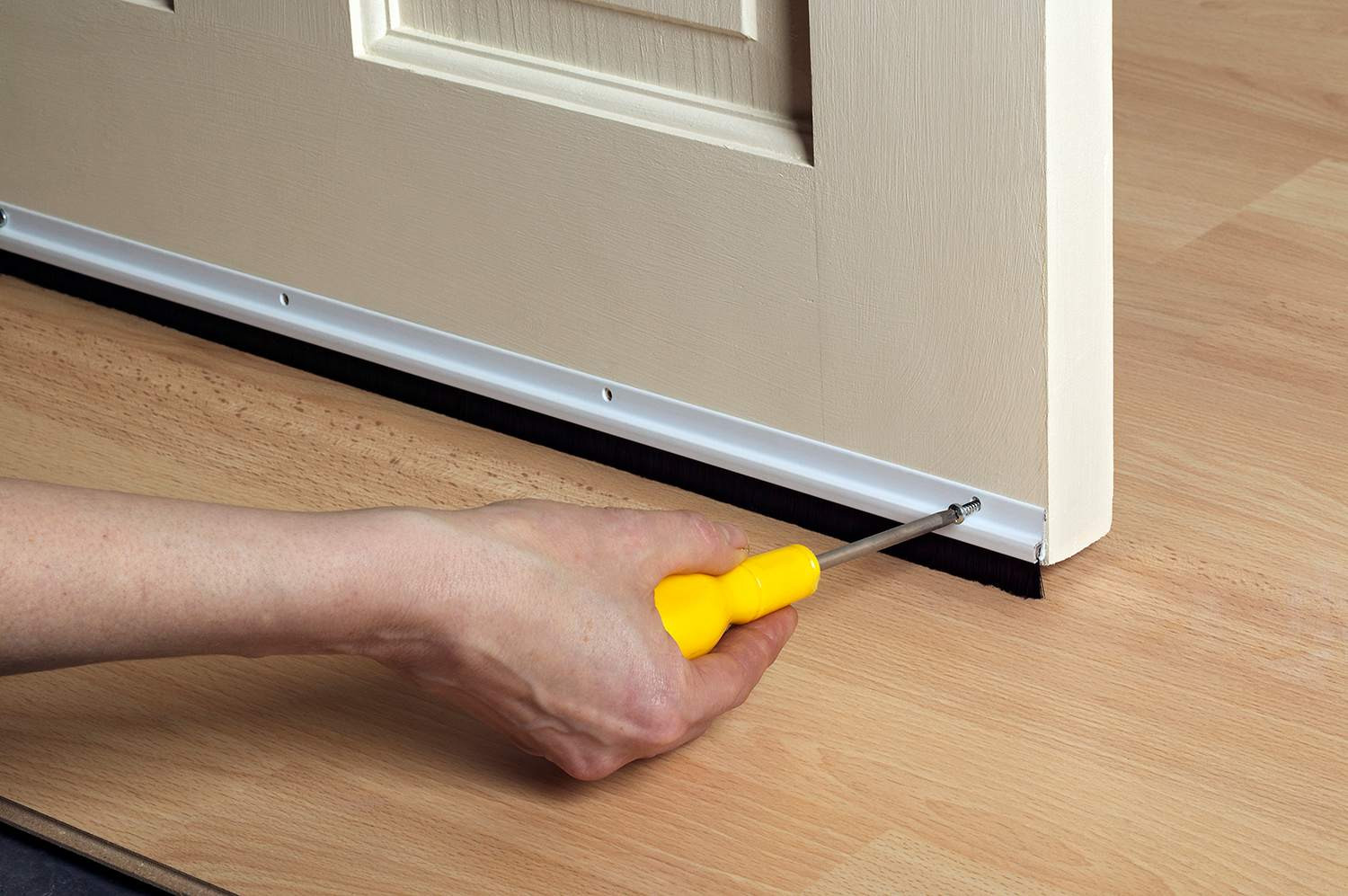 best way to fill gaps in hardwood floors of 10 ways to bug proof your home pertaining to man screwing brush seal to edge of door