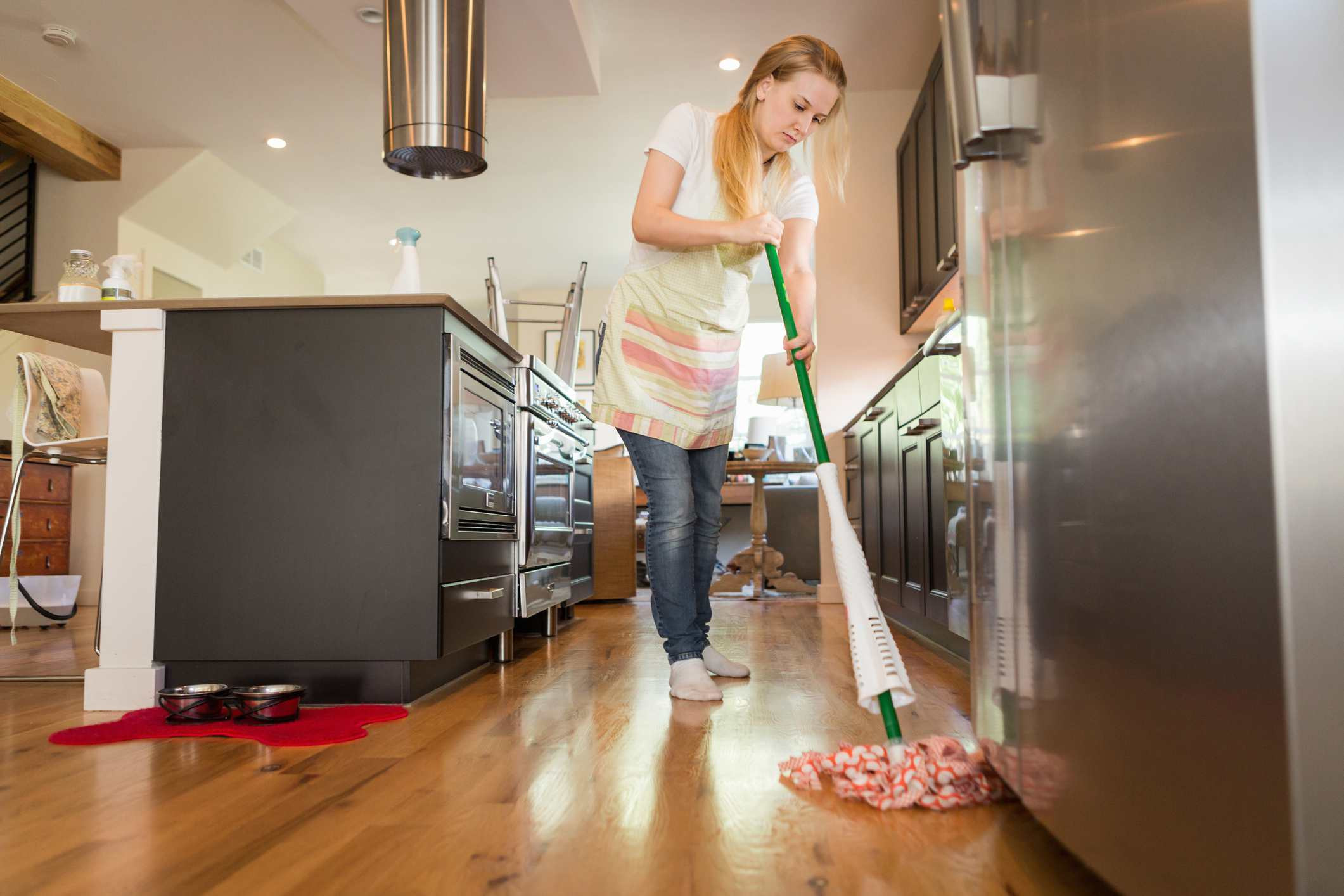 can you clean hardwood floors with vinegar and water of 9 laminate floor cleaning mistakes and how to fix them for a woman mopping the floor