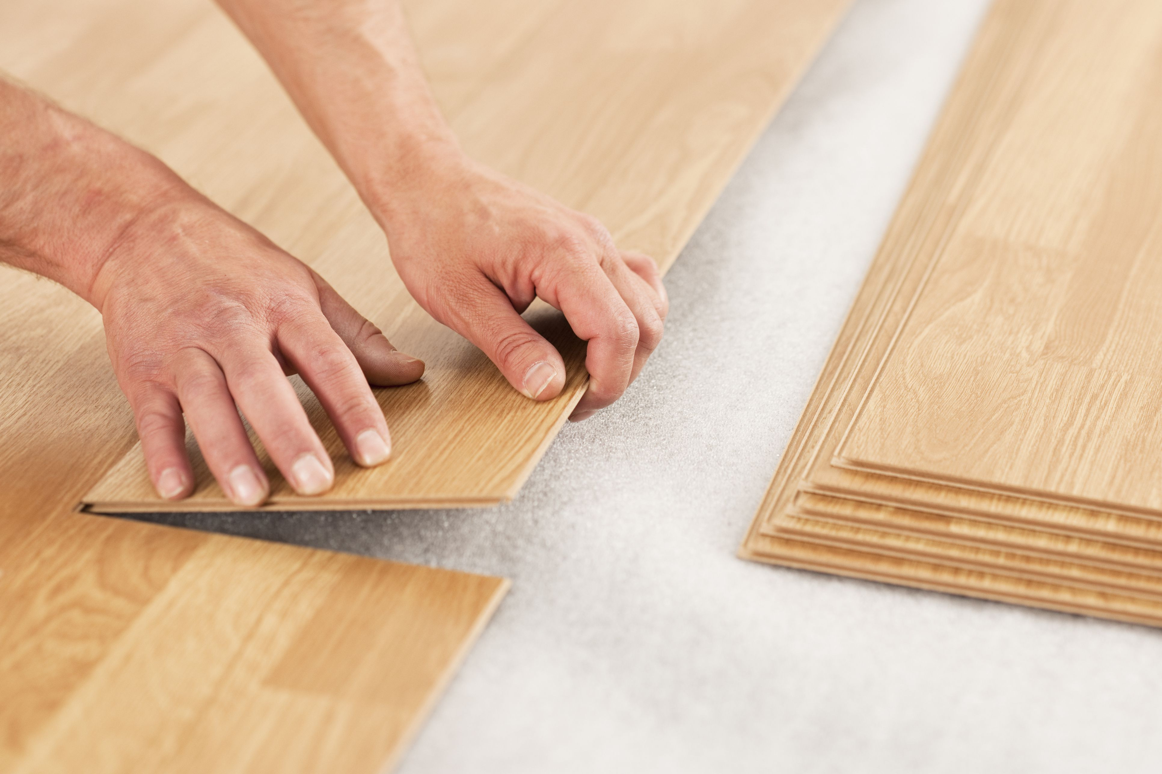 cleaning shaw engineered hardwood floors of how to reduce and prevent static on laminate flooring pertaining to picture of man s hands laying yellow laminate flooring 154961561 5875738e3df78c17b6de8341