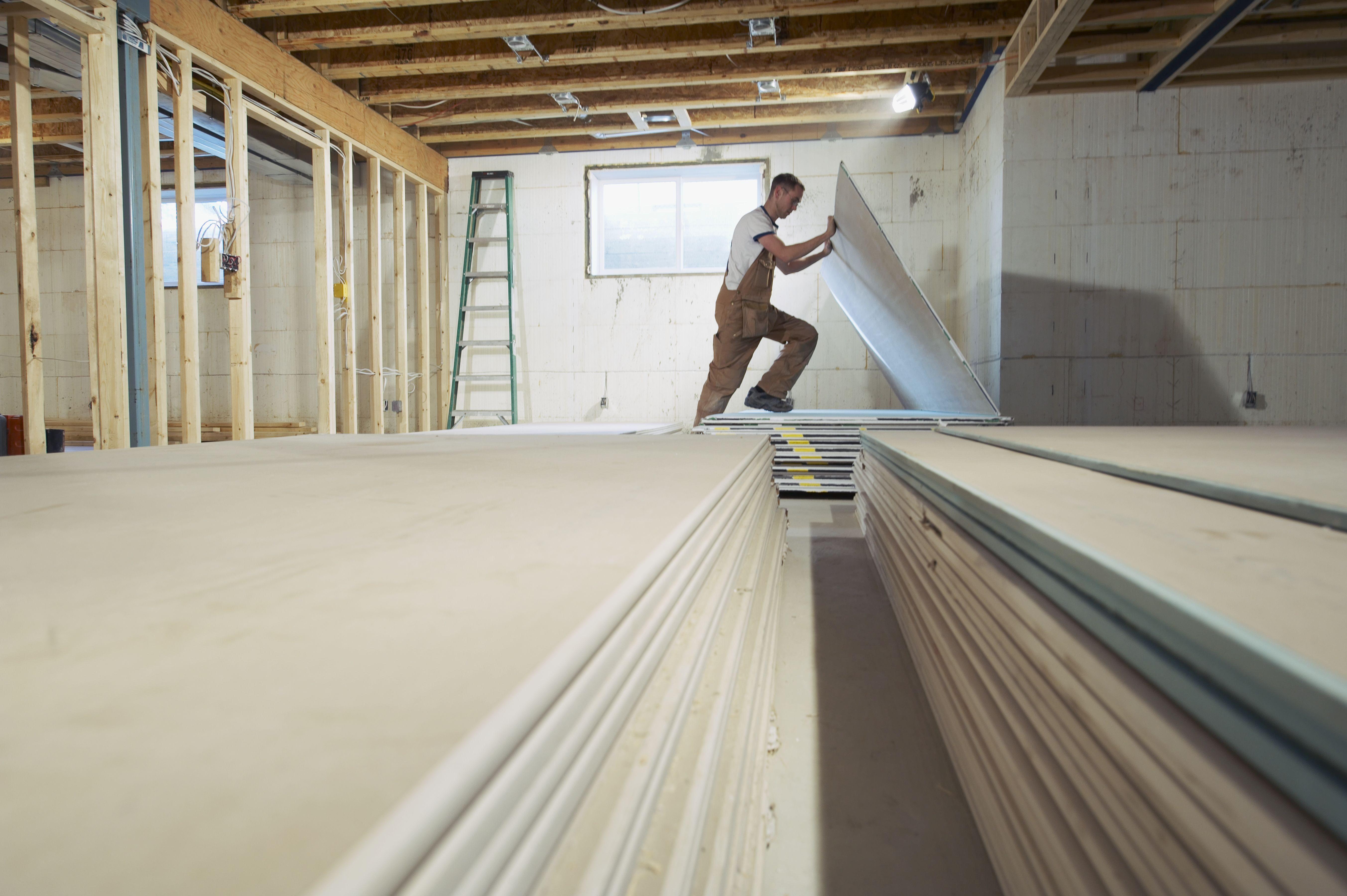 cost of hardwood floors for 2000 sq ft of average basement finishing cost inside man installing drywall in new house 522951112 5b12da6dba6177003d66594d