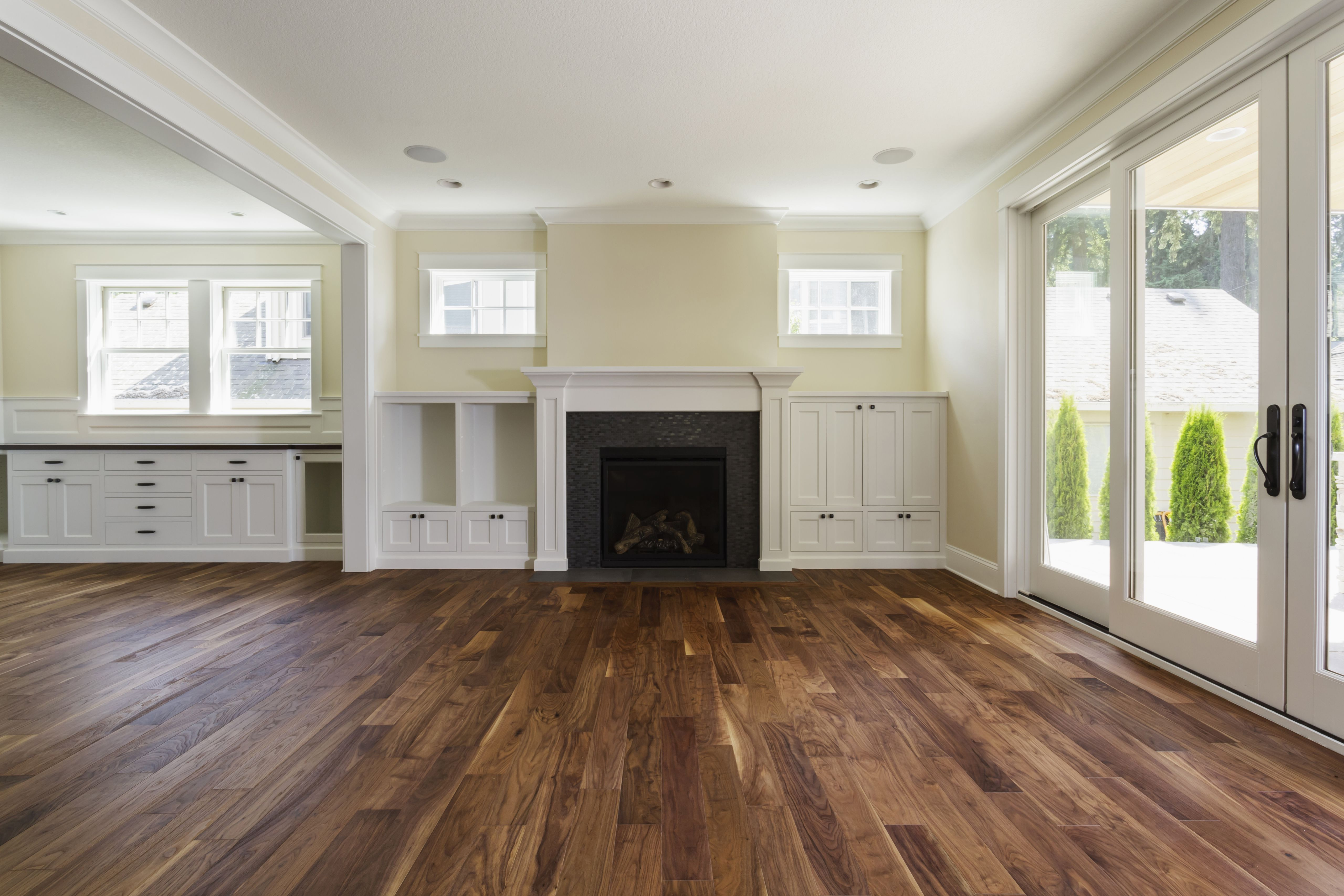 grey hardwood floors in living room of the pros and cons of prefinished hardwood flooring inside fireplace and built in shelves in living room 482143011 57bef8e33df78cc16e035397