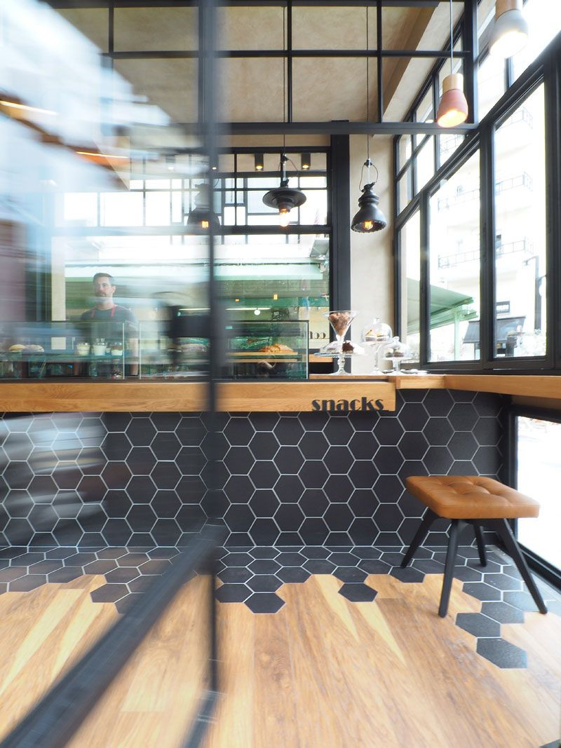 hardwood floor transition between uneven rooms of hexagon tiles transition into wood flooring inside this cafe in in inside this cafe black hexagon tiles wrap from the counter to the floor where they meet wood laminate flooring