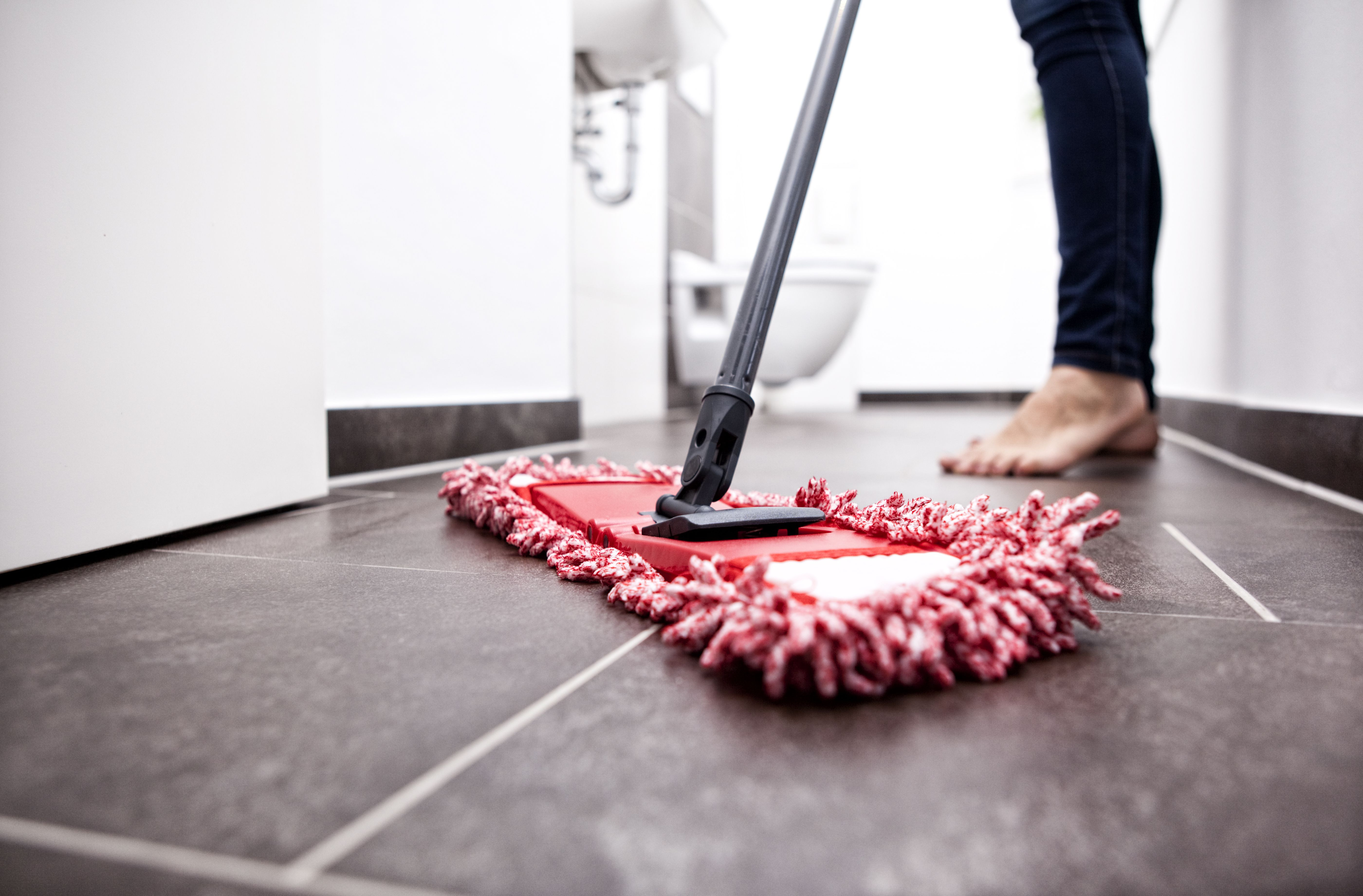 how to keep hardwood floors clean of what to know about cleaning self adhesive floor tiles in woman wiping the floor in bathroom 588494491 5a70f8fe43a1030037b47d0b