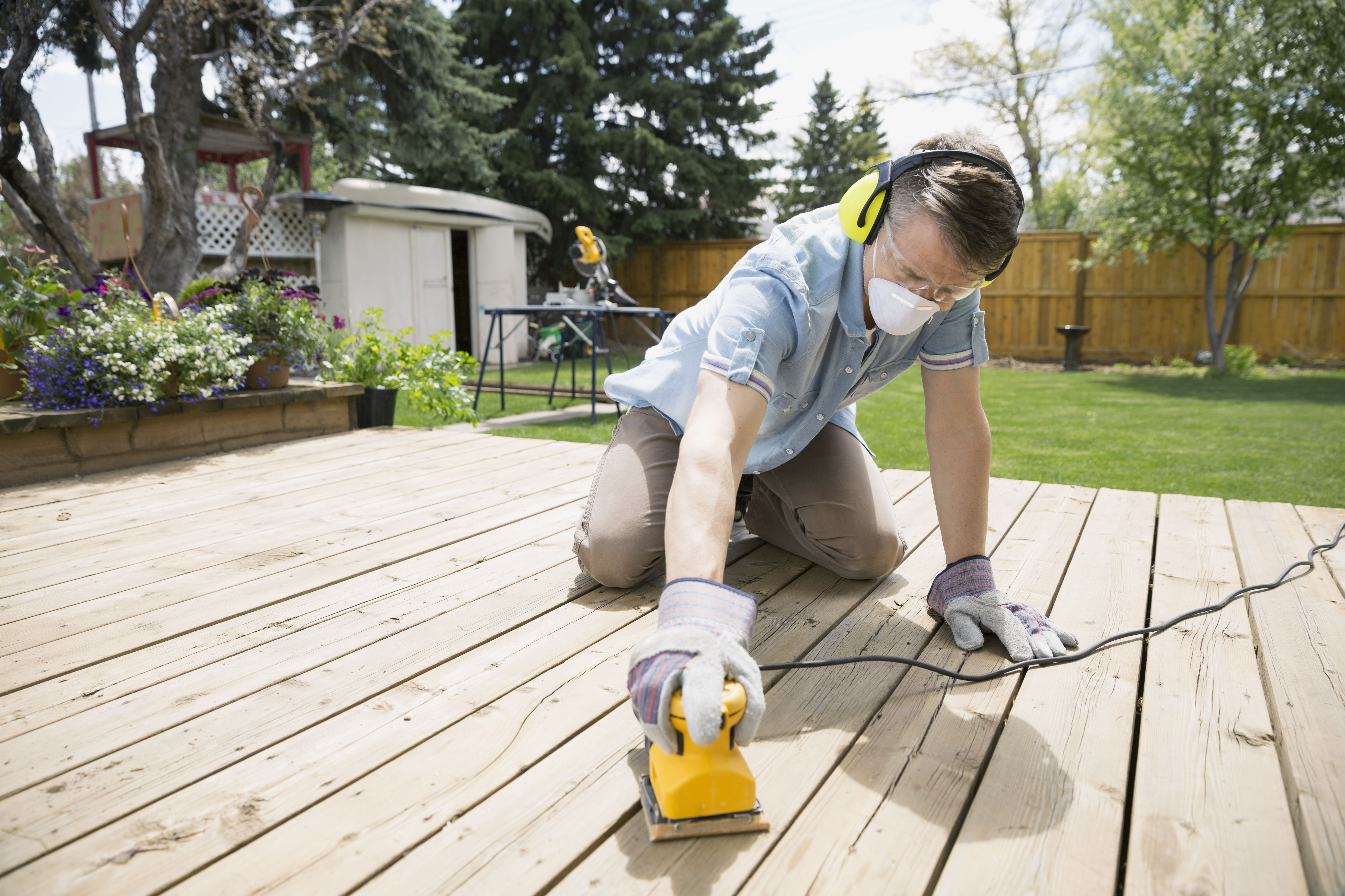 refinish hardwood floors or paint first of refinishing a wood deck an overview for man sanding backyard deck 500817135 5810fe043df78c2c7315c92b